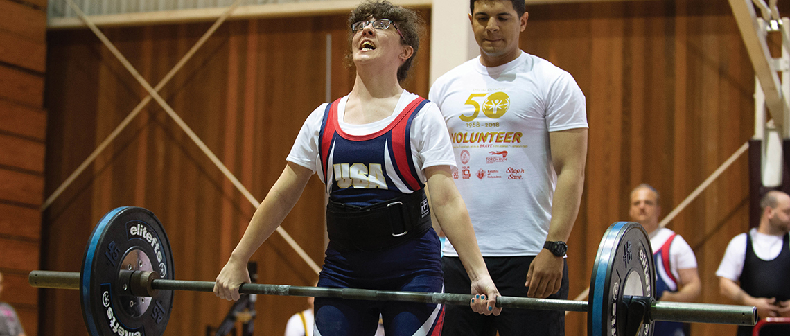 Female athlete grimacing while lifting heavy weights during a competition